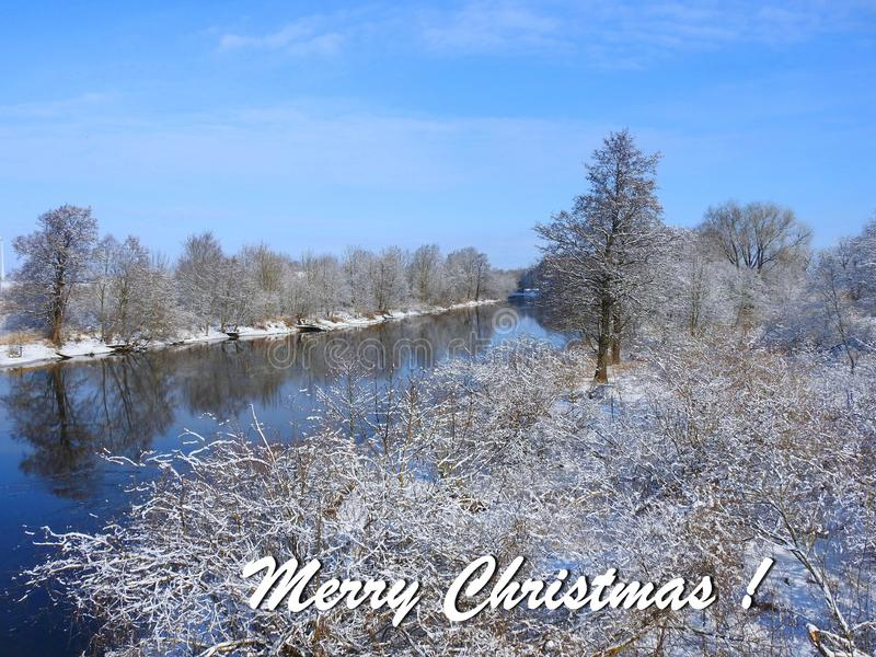 Merry Christmas card done using trees and river , Lithuania. Beautiful natural snowy trees, river Minija and note - Merry Christmas stock photo