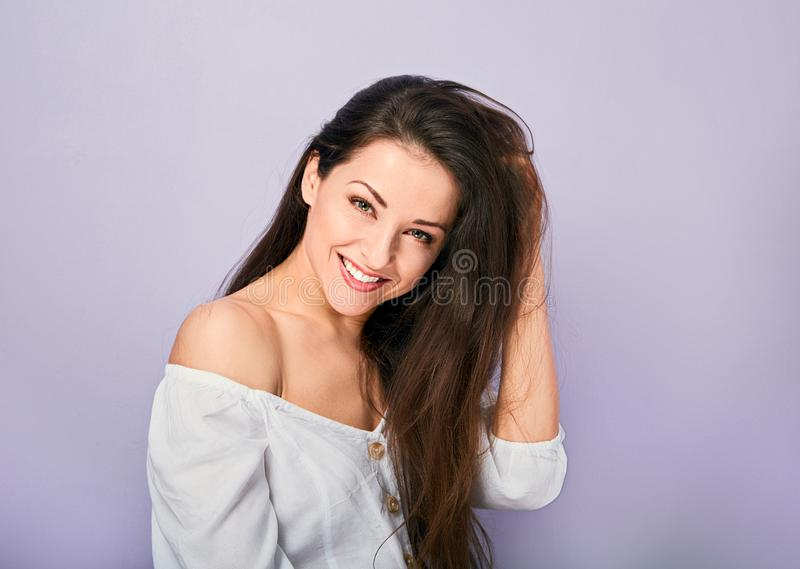 Beautiful natural toothy smiling woman looking with happy in white shirt with long curly hairstyle. Closeup portrait royalty free stock photo