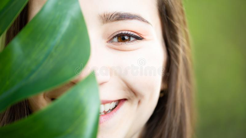 Beautiful natural young woman closeup behind big monstera leaf with green background in the woods stock photos