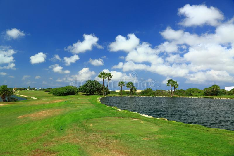 Beautiful nature landscape of Aruba island. Green grass, lake and blue sky with white clouds stock image