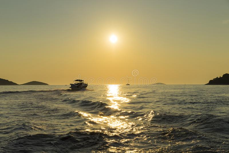 Beautiful nature and landscape photo of boat in sunset at Adriatic Sea in Croatia. Nice warm summer evening with sun low at horizon. Waves and reflection in stock images