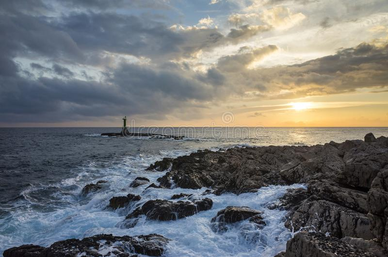 Beautiful nature and landscape photo of small lighthouse and reef in Adriatic Sea Razanj Croatia. Lovely colorful outdoor evening at sunset. Nice cloudy sky stock photo