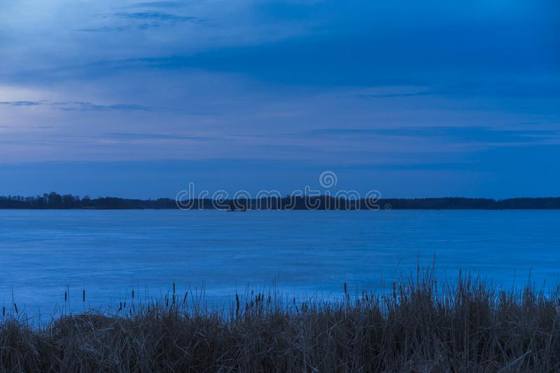 Nice fresh blue dusk sky at sunset and ice lake in Sweden. Beautiful nature and landscape photo of spring evening in Sweden Scandinavia Europe. Nice fresh blue royalty free stock image