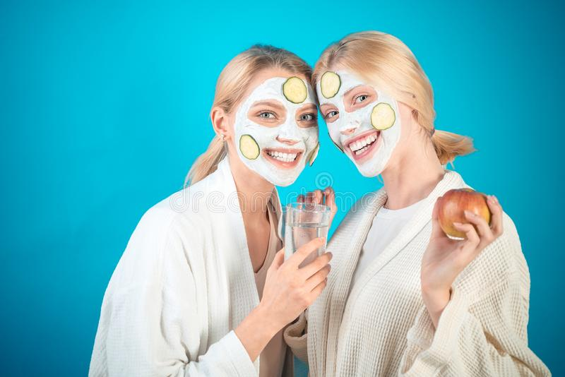 Beautiful nature smiling blonde women friends stand face to face and make healthy spa skincare. Happy friendship and stock images
