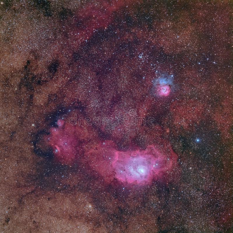 Beautiful nebulae in rich Milky way star field in the constellation Sagittarius including M8 the Lagoon nebula, M20 the Triffid ne royalty free stock photo