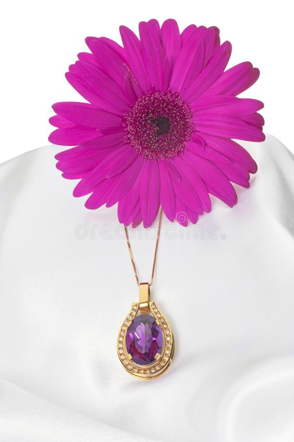 Arrangement of flower with precious stone. A beautiful necklace with amethyst in satin with white background. Amethyst is considered the birthstone of February stock photo