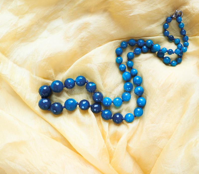 Beautiful necklace of dark blue faceted agate on yellow silk stock image