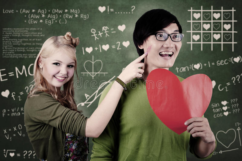 Beautiful nerd girl and guy in love at school stock images