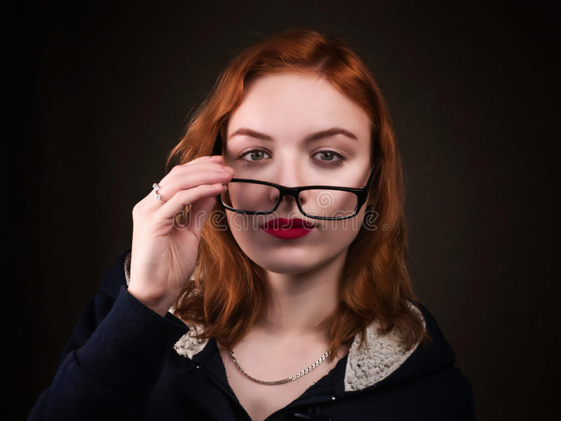 Beautiful nerd girl or young woman looking over eyeglasses royalty free stock photography