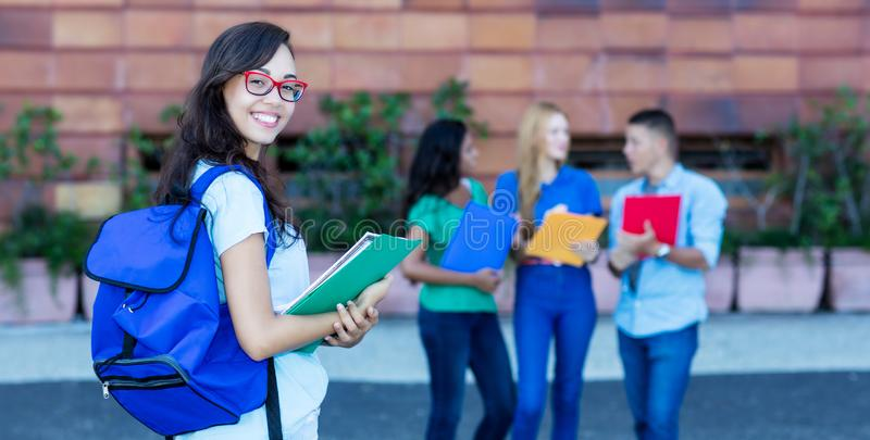 Beautiful nerdy german female student with group of students stock photo