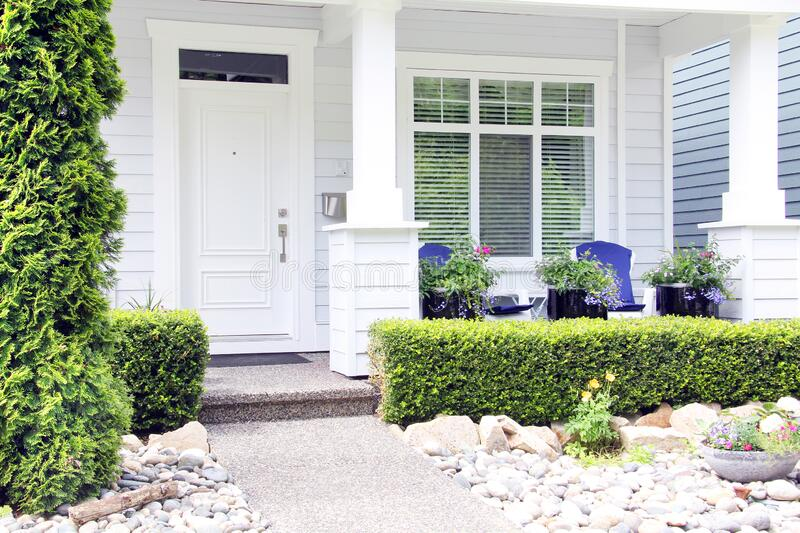 Beautiful new contemporary white home in a Canadian neighbourhood. Front door with a pretty porch and rock garden stock photos