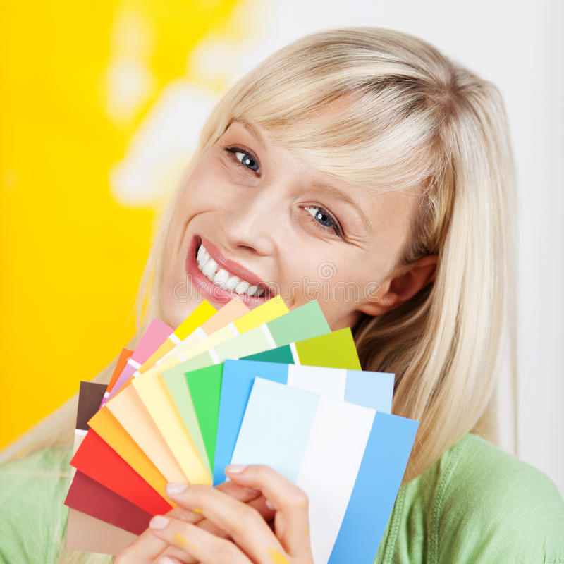 Beautiful new paint colours. Gorgeous blonde woman holding up a selection of beautiful new paint colours on swatches when renovating and decorating her house royalty free stock images