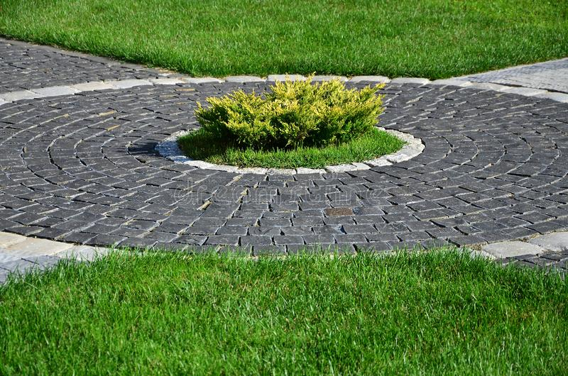 A beautiful new walkway made of paving stone is located among the green gras. S stock photography