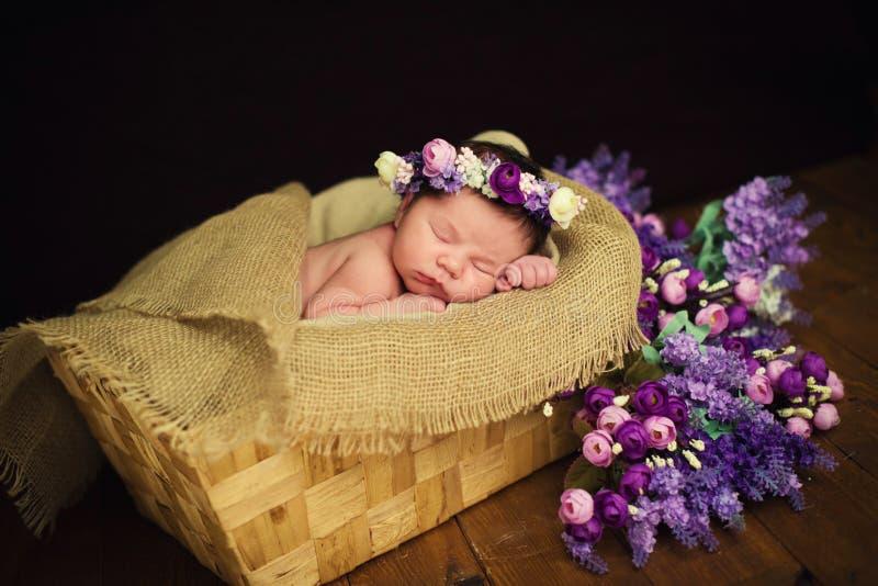 Beautiful newborn baby girl with a purple wreath sleeps in a wicker basket royalty free stock photos