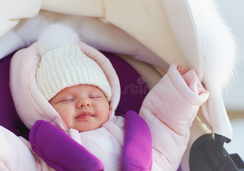 Beautiful newborn baby girl sleeping peacefully in pram during a winter walk stock image