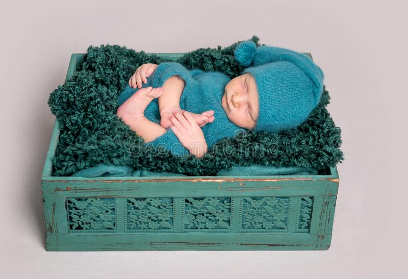 Newborn baby lying in wooden crate stock photography