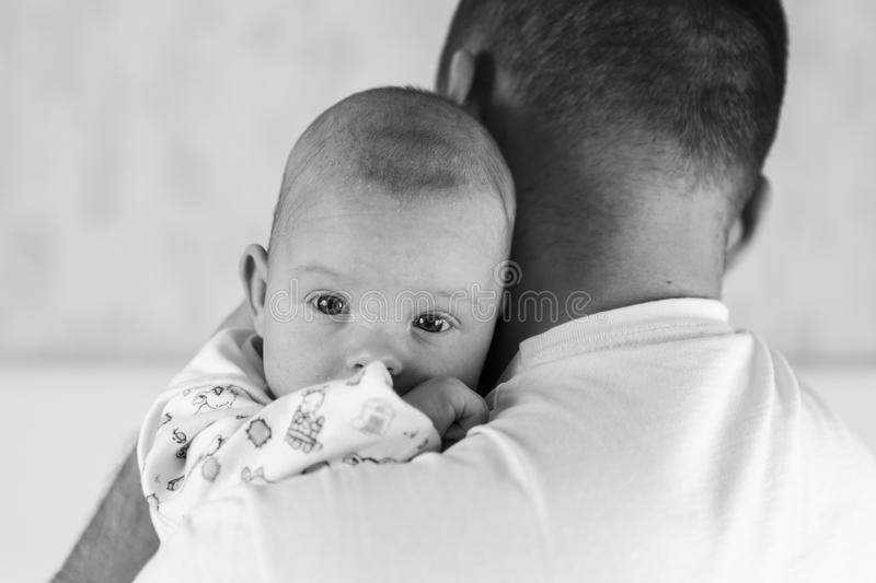 Beautiful newborn baby. Portrait of a beautiful white blue-eyed newborn baby in the hands of Dad close up stock photo