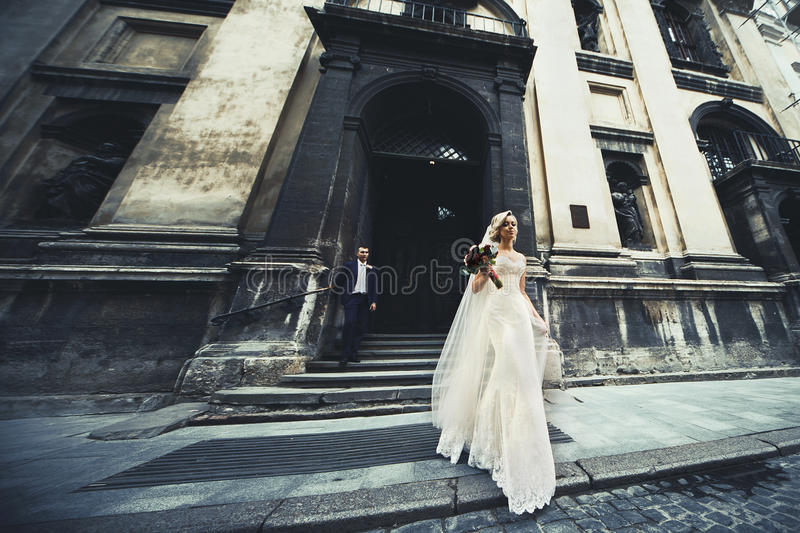 Beautiful newlywed couple posing near old church, elegant bride stock photography