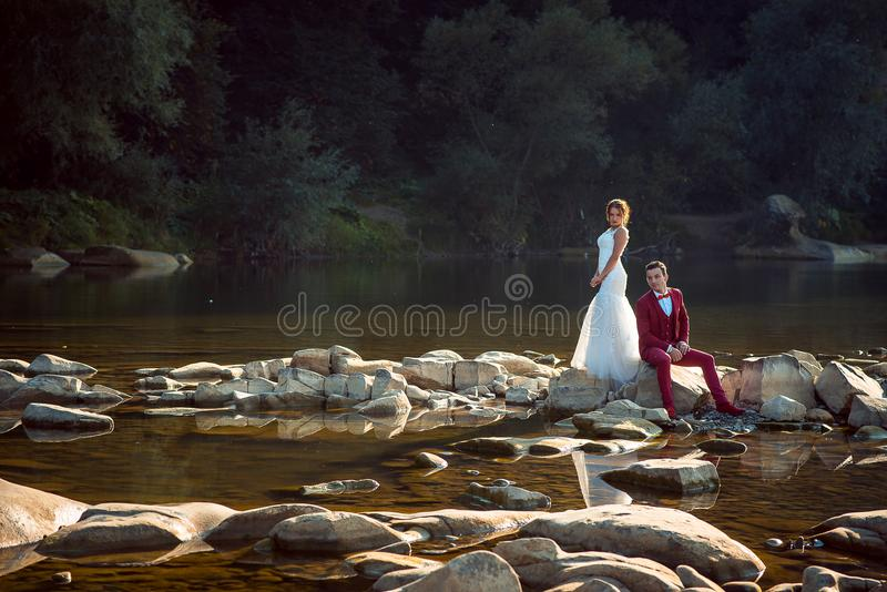 Beautiful newlyweds are posing at camera during the sunset. The charming red head bride is standing near the sitting. Groom on the riverstones stock image