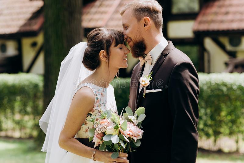 Newlyweds are smiling at each other. Newlyweds stand forehead to forehead royalty free stock images