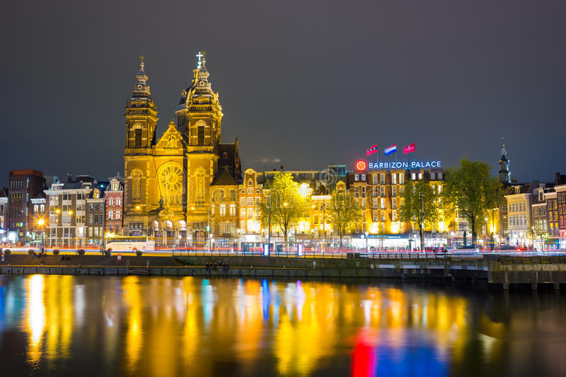 Beautiful night in Amsterdam. Night illumination of buildings and boats near the water in the canal. stock photos