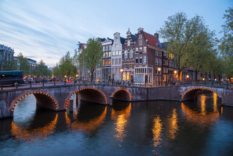 Beautiful night in Amsterdam. Night illumination of buildings and boats. stock photography