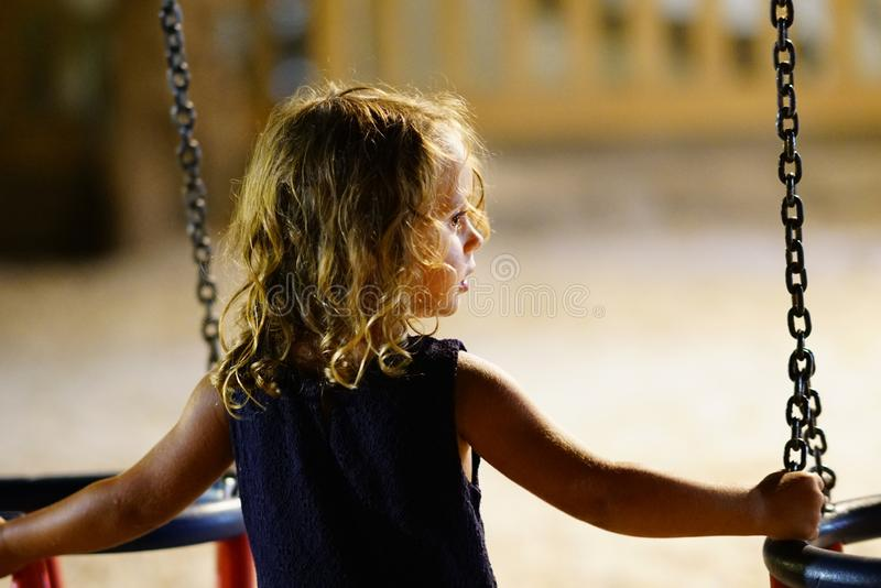 Beautiful night backlight of a three-year-old girl playing with a swing. In a playground closeup lovely white female outdoor fun kid people beauty thinking you royalty free stock photos