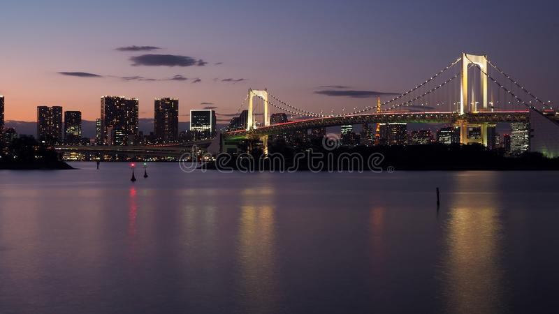 Beautiful night city scape of Tokyo bay with Tokyo rainbow bridg. E and motion blurred of car traffic lights royalty free stock photo