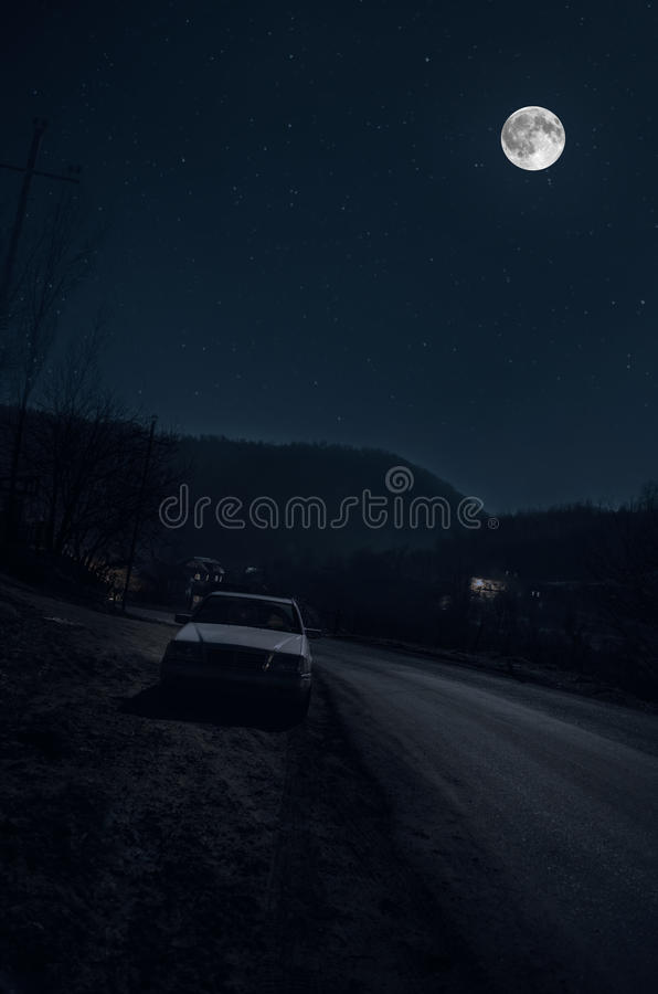 Beautiful night landscape of big full moon rising over the mountain road with hill and trees, with car near road. Beautiful night landscape of big full moon royalty free stock image