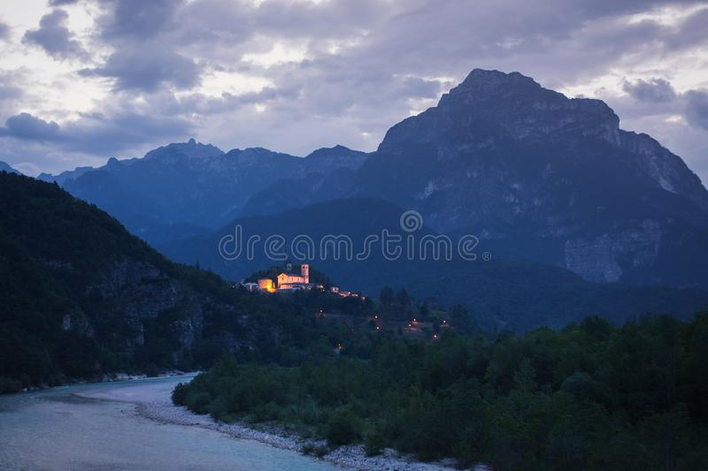 Beautiful night landscape with fjords in Italy. Church on mountain. Europe. Evening village with backlight. Twilight in the royalty free stock image