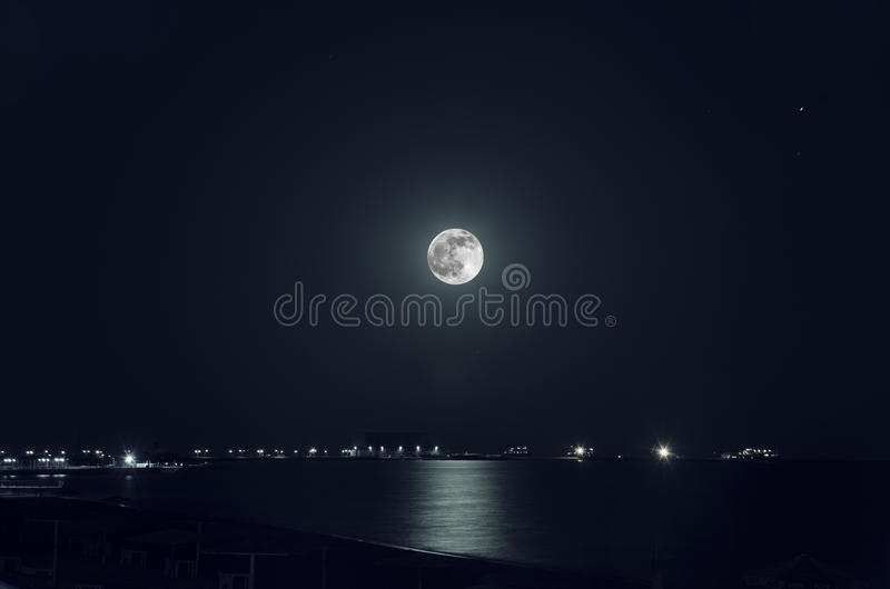 A beautiful night landscape of full moon over dark water with reflections on it royalty free stock photography