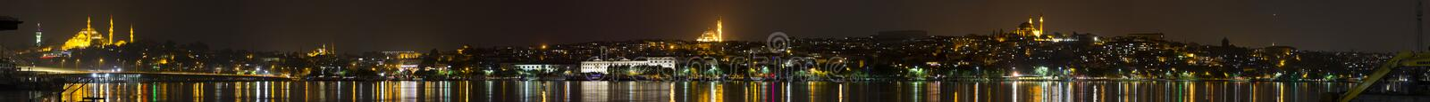 Beautiful night panorama of the Istanbul city. From a river shore with four shining mosques in the background and a reflection on the water royalty free stock photography