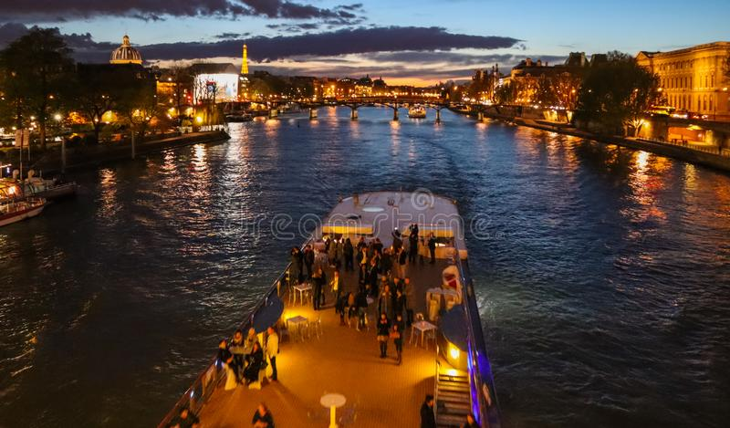 Beautiful night Paris, sparkling Eiffel tower, bridge Pont des Arts over the River Seine and touristic boats. France.  royalty free stock images