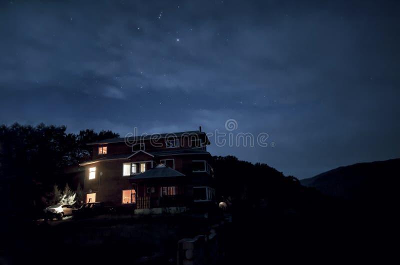 Beautiful night scene of a lone house with lights on windows. Azerbaijan. Masalli. Vilesh lake. Talish mountains stock photography