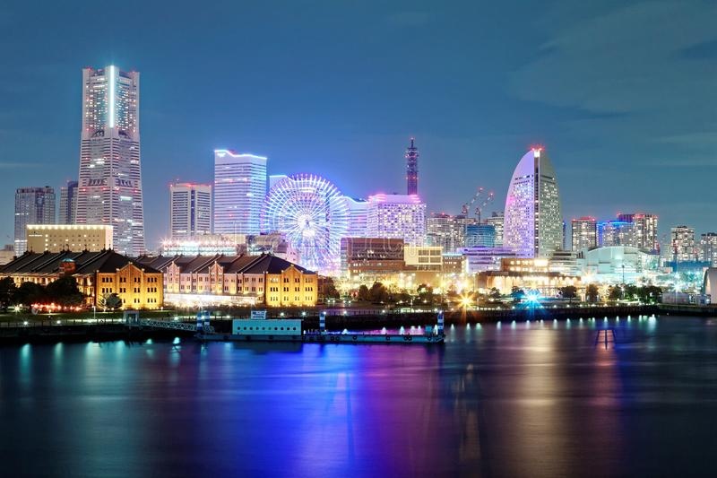 Beautiful night scenery of Yokohama Minatomirai Bay area with high rise buildings in the background. A giant Ferris wheel in Cosmo World Amusement Park & royalty free stock image