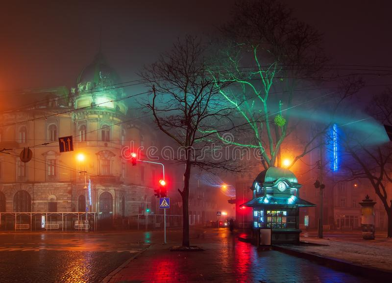 Beautiful nightscape of city center of Lviv, Ukraine at foggy night. With wet pavement and newsstand on foreground. UNESCO world heritage site stock photos