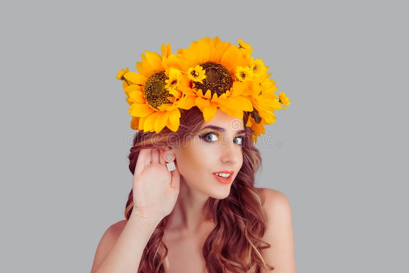 Woman with floral headband puts a hand to the ear to hear better stock photography