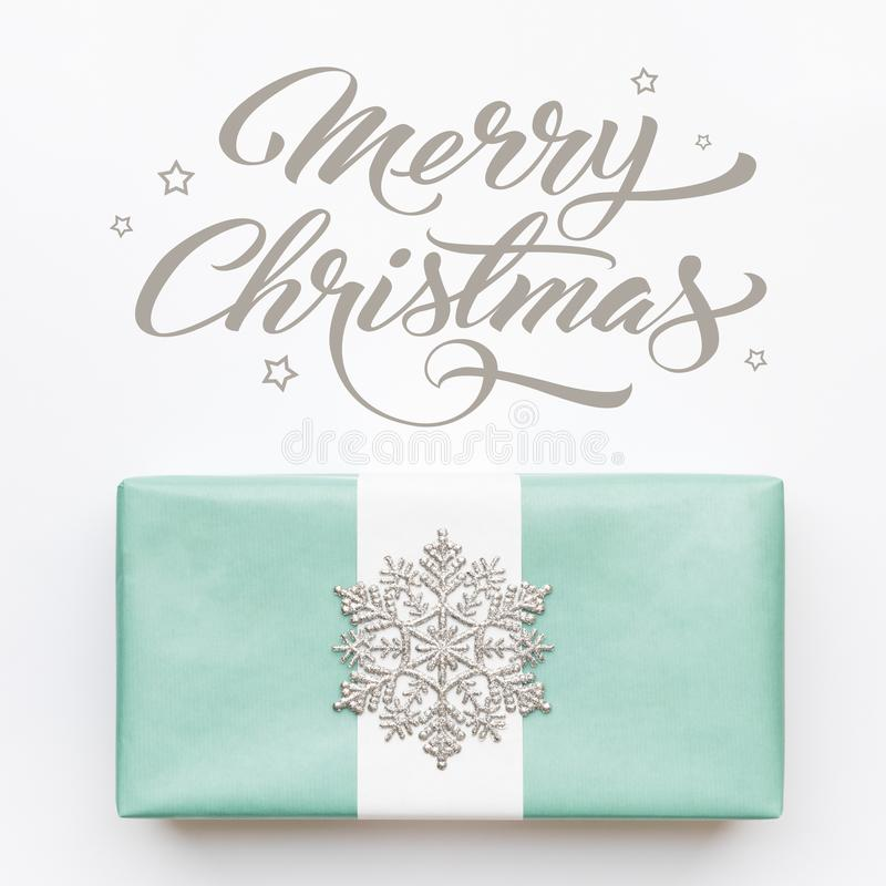 Beautiful nordic christmas gift with silver snowflake isolated on white background. Turquoise colored wrapped xmas box. royalty free stock image