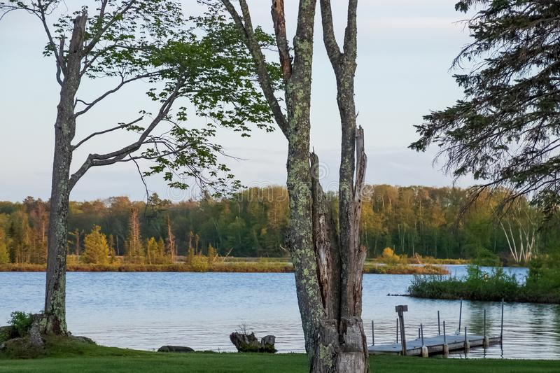 Beautiful Northwoods scene at shoreline of Chippewa Flowage with pier jutting into water and gorgeous trees in Hayward. WI royalty free stock photo