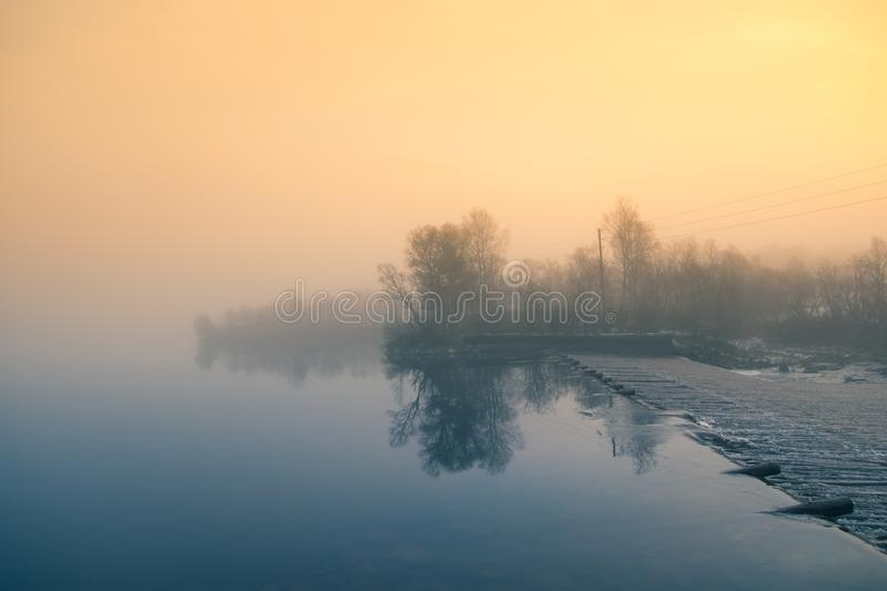 A beautiful Norwegian autumn scenery. Misty morning on a lake. Water flowing over the dam, waterfall. stock images