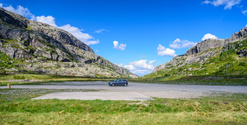 Beautiful Norwegian landscape in the mountains - single car parked in the centre. Beautiful panorama of a mountain valley in Norway with forests in the royalty free stock photos