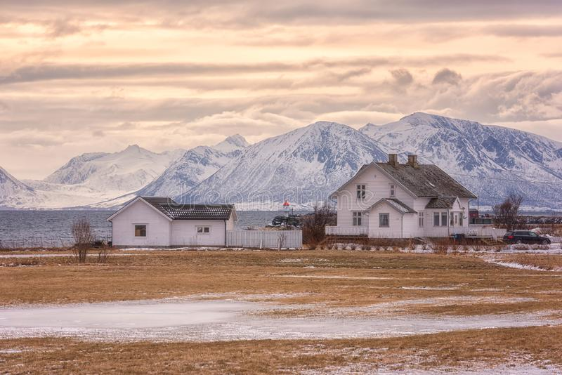 Beautiful norwegian winter sunset landscape, white house on the seacoast on the snowy rocky mountains background stock photography