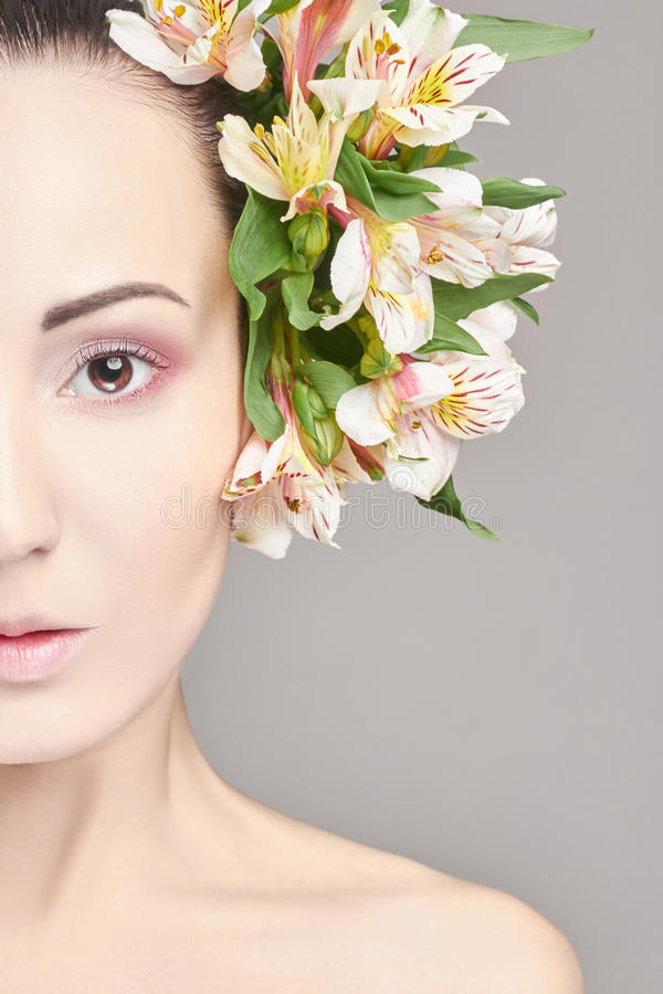 Beautiful Nude attractive brunette with flowers on his head. Fashion beautiful makeup, clean skin, facial care. Portrait of young. Beautiful woman with perfect royalty free stock photo