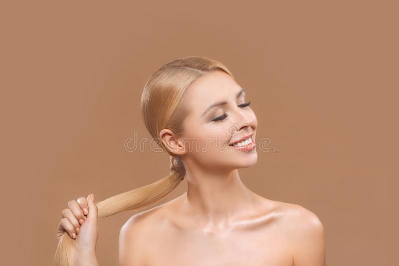 Beautiful nude blonde woman with long hair and closed eyes,. Isolated on brown, haircare concept royalty free stock images