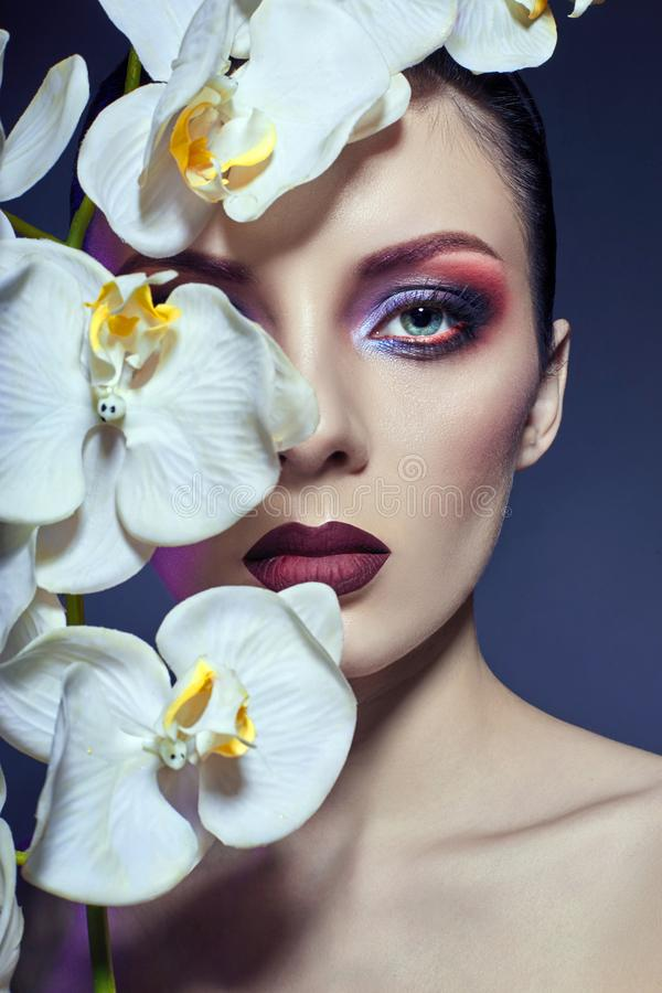 Beautiful Nude woman with a branch of white Orchid in her hands, bright contrasting makeup on the eyes and lips. Contrasting colo stock images