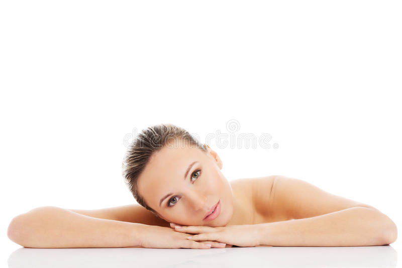 Beautiful nude woman is lying on her hands. Isolated on white stock image