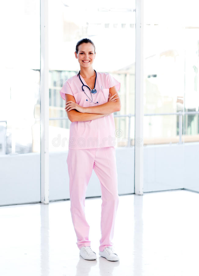 Beautiful nurse standing with folded arms. Isolated beautiful nurse standing in front of the camera with folded arms royalty free stock photos