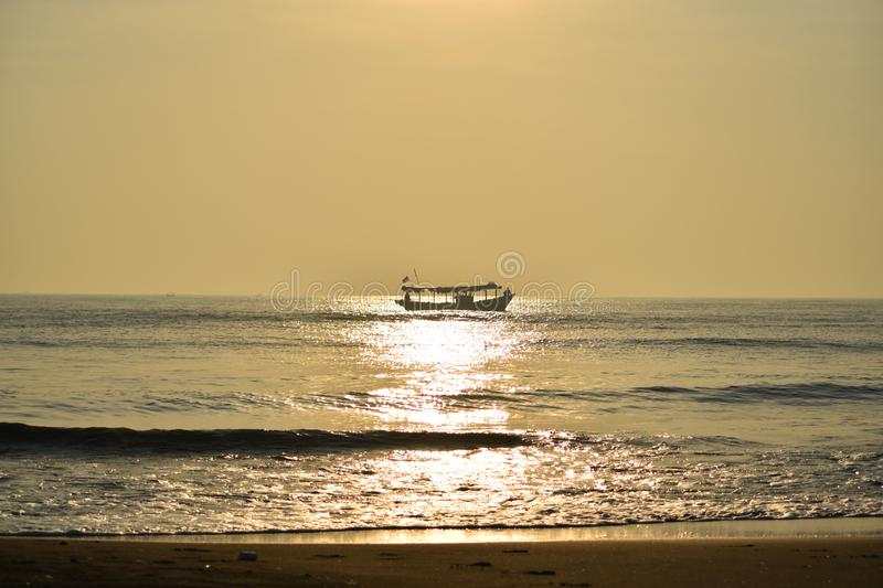 Beautiful ocean in the morning. The beauty of gold from the sun rises, illuminates the boats of the fishermen, the beach of Tanjung pasir, Tangerang Selatan royalty free stock photography