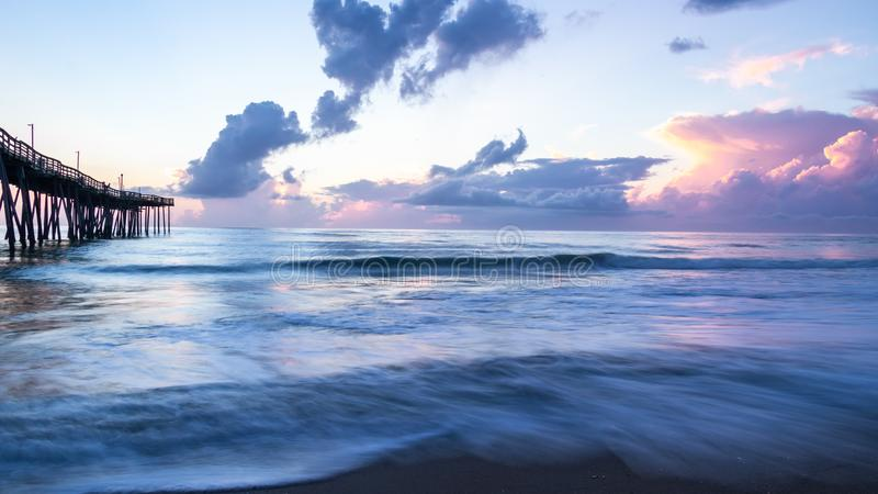 Beautiful ocean sunrise and gentle waves beside an old wooden fishing pier extending far out into the sea. stock photo
