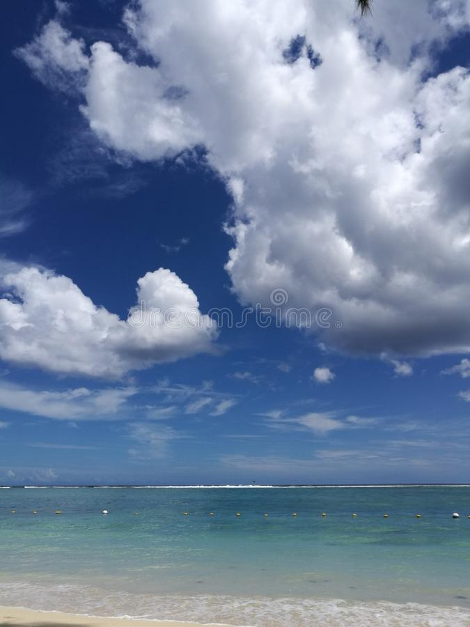 Beautiful ocean view with torquise water and dramatic clouds on sky royalty free stock photography